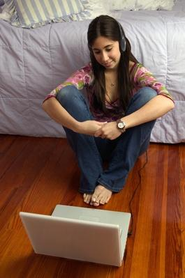 Teenage girl (16-18) on bedroom floor, listening to music on laptop | Home Entertainment Technologies