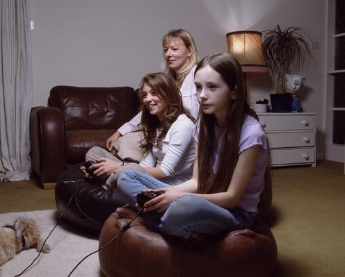 Two sisters (11-14) playing video game, mother sitting in background | Social Gaming: From Arcades to Online