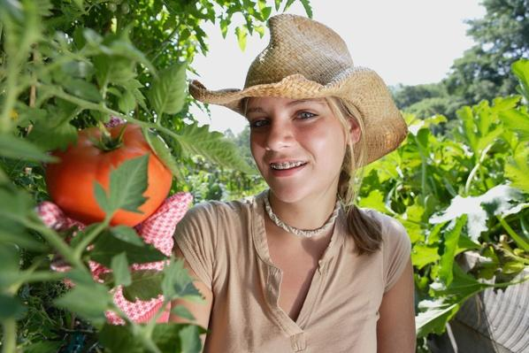 Teenage Girl (14-16) Picking Tomato in Community Garden | Earth's Resources