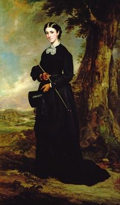 Young woman wearing a black riding habit and standing in a landscape