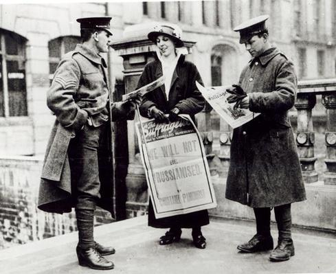 A Suffragette selling newspapers to two soldiers, c.1914