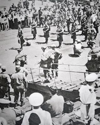 Kilted pipers play ashore from the 1st Battalion Argyll and Sutherland Highlanders from HMS Ceylon at Pusan, 29th August 1950