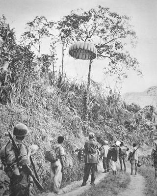 French and Vietnamese soldiers recover supplies parachuted to them, during the siege of Dien Bien Phu, November 1953-May 1954