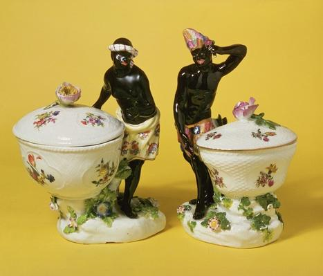 Two Meissen blackamoors standing by sweetmeat baskets and covers, 1741