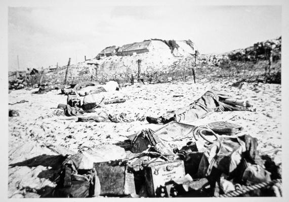 Dead bodies and equipment lie scattered on a beach in front of a German bunker, 6th June 1944