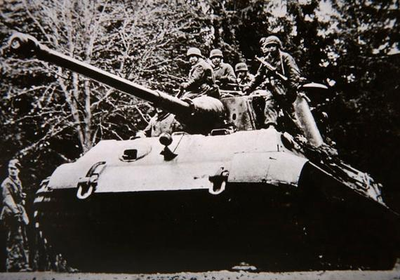 Tiger II German heavy tank carrying paratroops advances through Ardennes forest, December 1944- January 1945