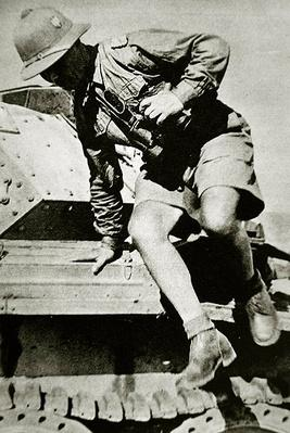 Rommel, in early tropical helmet & shorts of the Afrika Korps, jumps down after inspecting a captured British Crusader tank, 1941