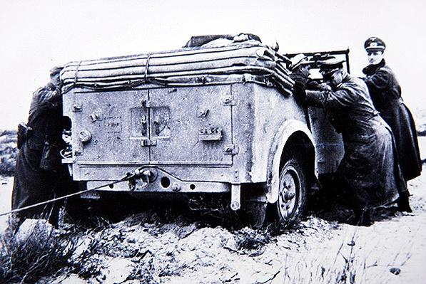 Erwin Rommel helps to push his command vehicle out of the sand in North Africa