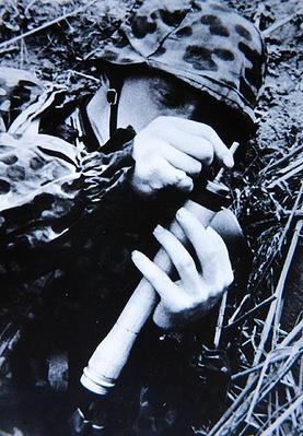 WW2 German soldier inserting detonator into a stick grenade