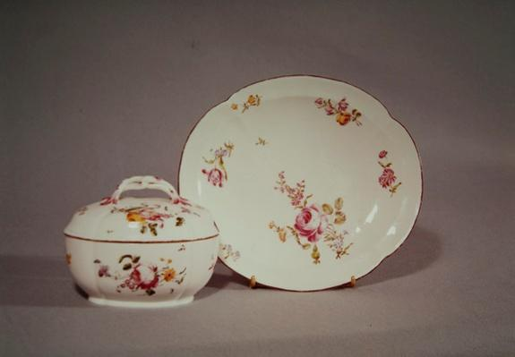 Mennecy Sugar bowl with its quatrefoil shaped charger, decorated with a multicoloured flower design