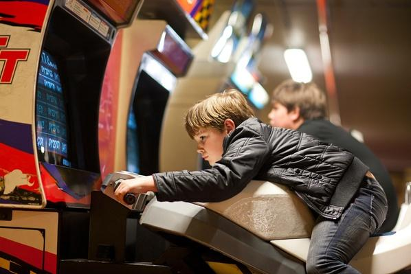 Two young brothers playing on driving video games | Social Gaming: From Arcades to Online