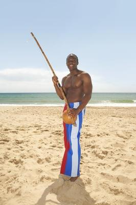Man with berimbau on beach | Musical Instruments