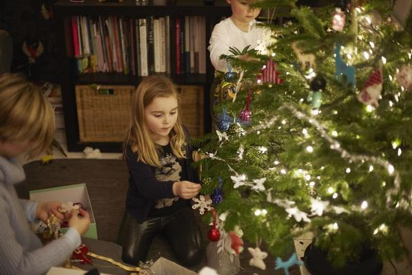 Young brother and sister decorating christmas tree | World Religions: Christianity