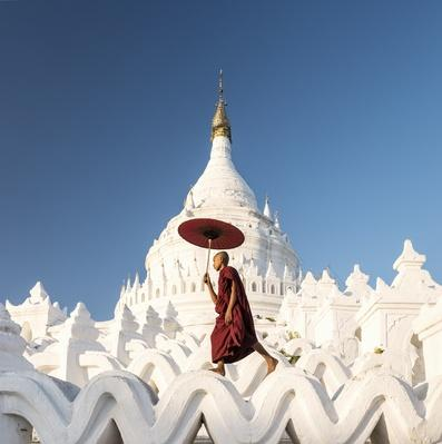 Buddhist monk walking across arches of temple | World Religions: Buddhism