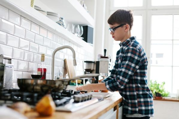 Teenage Boy Washing Up in the Kitchen | Earth's Resources