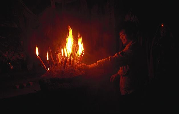 Man lighting incense at Han long Taoist temple | World Religions: Taoism