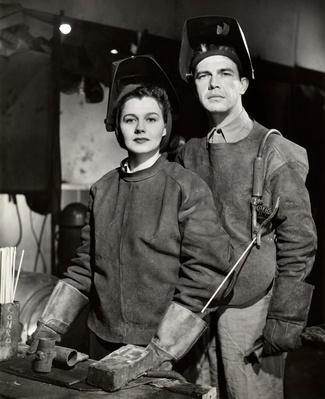 Couple in WW II defense plant with welding gear | World War II