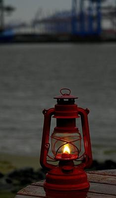 Close-Up of Lit Antique Kerosene Lantern By Lake at Dusk | Earth's Resources