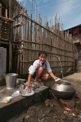 Woman Washing Cooking Pots Under Running Tap | Earth's Resources