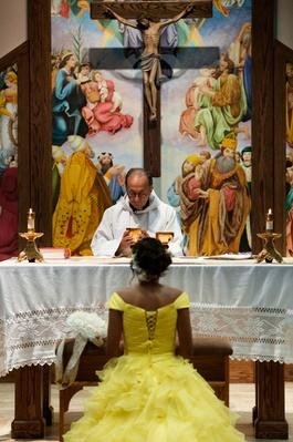 Hispanic girl celebrating quinceanera with priest in Catholic church | World Religions: Christianity