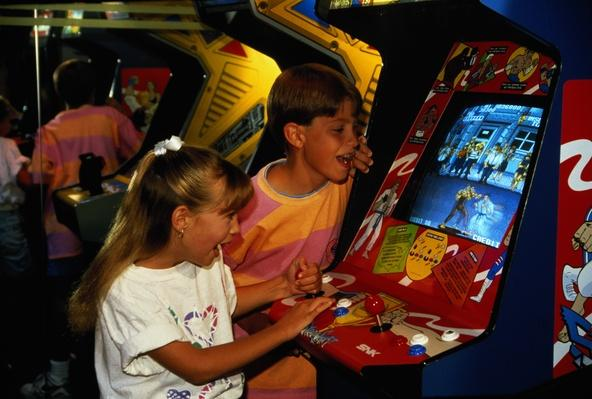 Boy (9-11) watching girl (7-9) playing on video game in arcade | Social Gaming: From Arcades to Online
