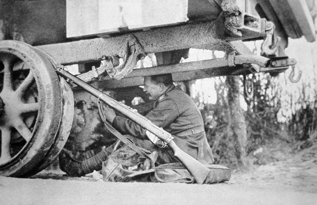 Mechanic of the British Army Service Corps repairing a truck with his 303 rifle close to hand, 1915