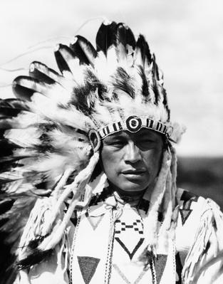 Sioux Native American man wearing large headdress | Native American Civilizations | U.S. History