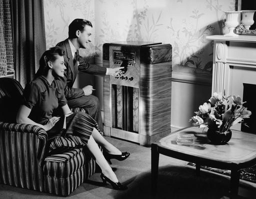 Couple listening to radio in living room, (B&W) | Home Entertainment Technologies