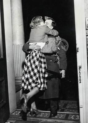 A soldier is greeted with a big hug and kiss from his ecstatic wife | World War II
