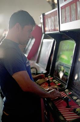 Man playing at video arcade | Social Gaming: From Arcades to Online
