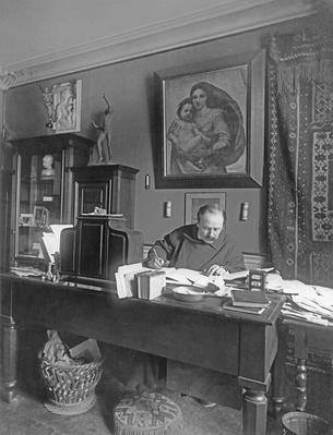 French composer Jules Massenet sitting at his desk