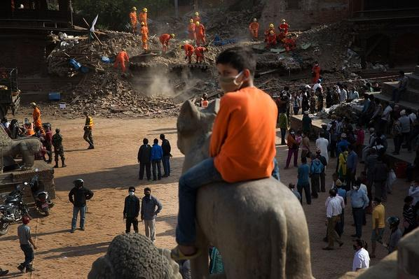 A Young Nepali Boy Sits Atop a Carved Statue Wathcing Rescue Teams | Global Oneness Project
