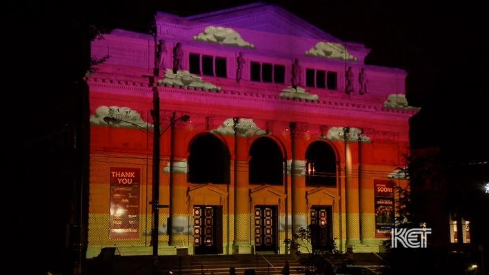 Image of projection mapping on building featuring rainbow colors and clouds.