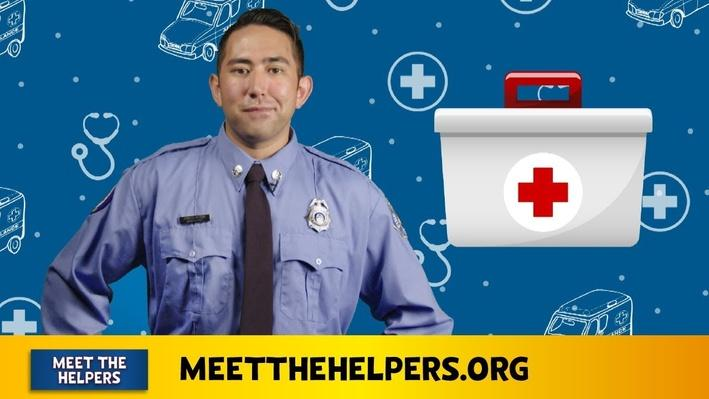 Man with long sleeve blue shirt, tie, badge, and nametag. Background has white and red first aid kit.