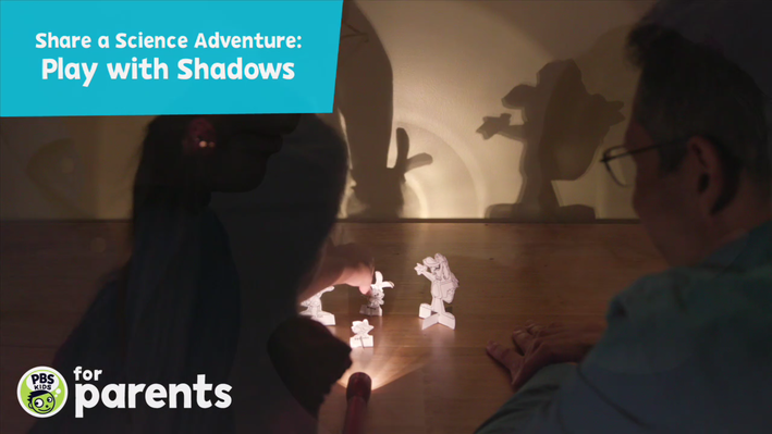 Image of father and daughter playing with Nature Cat shadow puppets