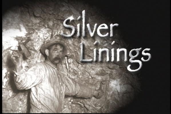Black and white historical photograph of late 19th century miner standing in a silver mine, wearing a striped shirt holding a hammer and pick