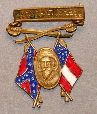 "Gold badge that reads ""John Hung Mogan Monument Committee."" It also shows crossed swords, Confederate and U.S. flags, and an image of John Hunt Morgan."