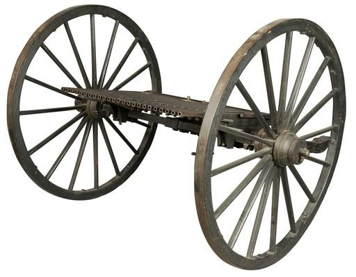 image of an early machine gun with 25 barrels set on two large spoked wheels