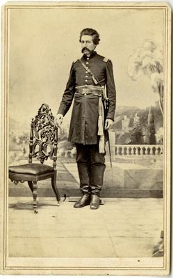 a photograph of a Union officer wearing his uniform stand in front of an ornate backdrop