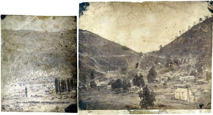 Black and white photo showing the Cumberland Gap which cuts through at the point where Tennessee, Virginia, and Kentucky meet. It shows farms, houses and trees at the base of mountains.