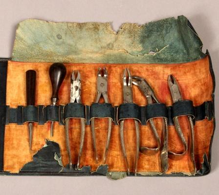 An orange and blank leather dental kit containing a chisel, knife, thread, and needles.