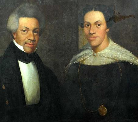 potraits of an african american couple dressed in a black suit and black dress with white lace details
