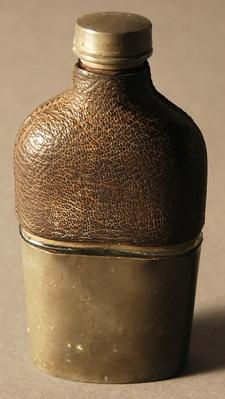 a glass flask covered in leather at the top and a tin cup at the bottom