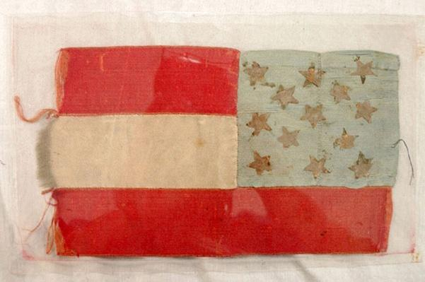 a sild handmade confederate flag with two red stripes, one white stripe and a blue square with 13 stars, arranged opposite the U.S. flag
