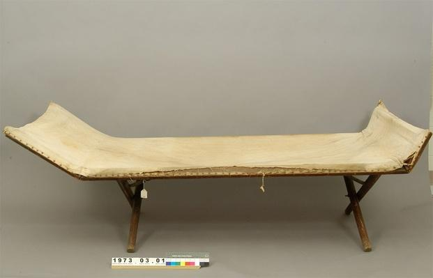 thin folding cot made of canvas on a wooden frame