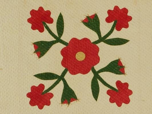 close up of square of a quilt featuring red flowers with green leaves