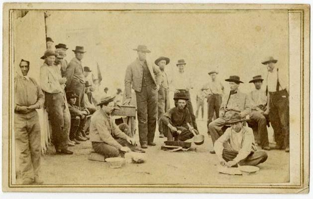sepia historical photo of a group of Confederate prisoners standing and sitting at a prison in Illinois