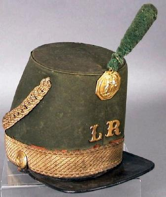 a tall brimmed hat with a flat top, plume, and various gold decorations worm by a group of militiamen