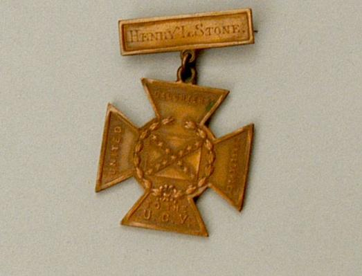 "a gold meda with a bar that reads ""Henry L. Stone"" with a gold cross hanging from it"
