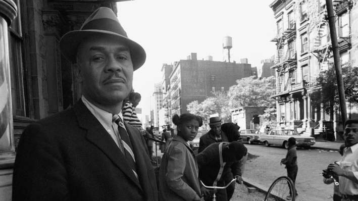 Ralph Ellison standing outside on a busy street